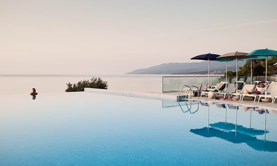 Dame som sitter å speider ut over havet i et infinity pool