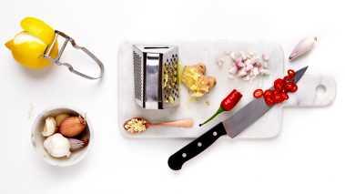 Skrell og finhakk løk og hvitløk. Fjern frøene fra chilien og skjær den i tynne strimler. Skrell det ytterste gule skallet av sitronen med en potetskreller og skjær i fine strimler. Finhakk ingefæren.