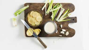 Sett ovnen på 180°. Skjær potetene i tynne skiver og purreløken i strimler. Press hvitløken. Stek løk og hvitløk myk i olivenolje i en kjele. Tilsett melk og kremfløte  og  kok  opp.  Legg  i  potetene  og  tilsett  salt  og pepper  etter  smak.  Kok  potetene  til  de  er  myke  og blandingen  er  tykk  og  kremaktig.  Glem  ikke  å  røre underveis