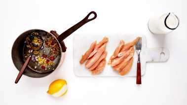Skjær kyllingfiletene i grove strimler. Hell olje i en stor kasserolle og legg i løk, hvitløk, ansjoser, ingefær, chili og sitronskall. Fres alt sammen i 2 minutter til løken har myknet.