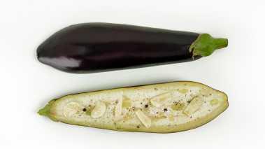 Sett ovnen på 225 grader, del auberginen på langs. Del hvitløken, og gni inn auberginehalvdelene med hvitløk og olivenolje, salte og pepre. Legg de på en stekeplate med bakepapir med snittflaten ned. Stek i ovnen i ca. 30 minutter til de er blitt lettstekte og myke. Snu auberginene og strø over sesamfrøene.  Kan også grilles på aluminiumsfolie under lokk.