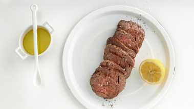 Skjær kjøttet i skiver og legg dem på et stort fat. Legg klatter av pestoen over kjøttet. Pynt med litt ruccola over, drypp over olivenolje, sitron og balsamicoeddiken.  Avslutt med  høvlet parmesan.