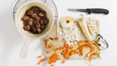 Skrell og skjær løk, persillerot og gulrøtter i terninger. Skjær kjøttet i biter på 2-3 centimeter.