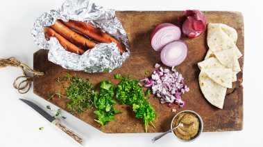 Finhakk urtene og bland i rødløk og sennep. Stek bratwürst- pølsene eller andre typer pølser og varm opp lompene. Legg en skje surkål på hver lompe, legg på pølse og topp med urtesennep.
