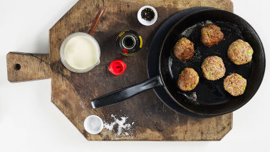 Fukt hendene og form farsen til store boller. Brun bollene i smør og olje i en panne til de blir fine og gylne.