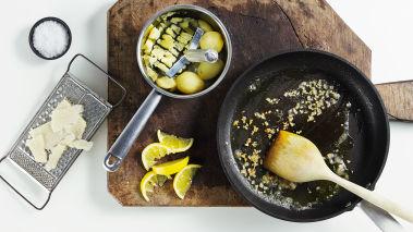 Kok potetene i saltet vann. Brun hvitløken i en stekepanne i 2 ss olivenolje. Hell vannet av potetene og knus dem med en potet-stamper. Smak til med hvitløk, sitron og et par spiseskjeer med olivenolje. Tilsett salt og pepper.
