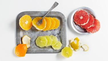 Skrell sitrusfruktene med kniv og skjær dem i skiver. Fjern eventuelle stener. Anrett skivene på et stort fat og stek valnøttene i en varm stekepanne i litt olivenolje.