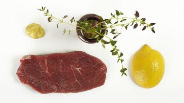 Gni kjøttet inn med timian, salt og pepper. Grill biffene i et par minutter på hver side. Legg biffene på et fat og la de hvile. Pensle på sennep og press over sitron før servering.