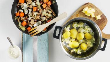 Sett ovnen på 200°. Skrell og skjær potetene i store biter. Del blomkålen opp i buketter. Kok blomkål og poteter i lettsaltet vann i 15-20 minutter til de er møre og hell av vannet (spar ca. 1 dl). Legg alt tilbake i kjelen. Tilsett 2 ss smør og litt av kokevannet. Mos potetene og blomkålen. Smak til med salt og pepper.