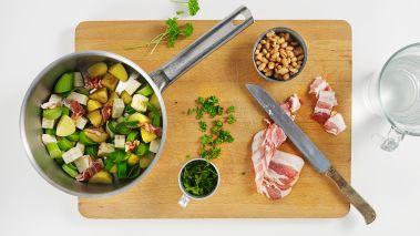 Sett ovnen på 225°. Skrell og skjær poteter, selleri og purre i grove terninger. Skjær baconet i strimler.