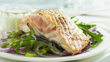 Legg opp laksen på et fat med råkost og ruccolaen lett blandet med dressingen, servere med kokte poteter eller brød.