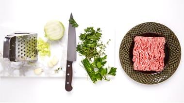 Riv gul løk og hvitløk på rivjern. Bland sammen ingrediensene til farsen og smak til med urter, salt og pepper.