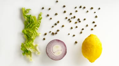 Riv salaten og fordel på 4 tallerkener. Pynt med hakket rødløk og kapers, og press over sitron. Legg opp den stekte svinefileten og drypp olivenolje over retten.