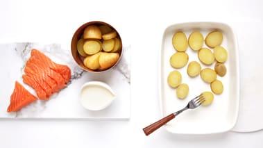 Sett ovnen på 225 grader. Legg de kokte potetene i en ovnsfast form, og trykk dem litt i stykker med en gaffel. Skjær laksen i tykke skiver på ca. 2 cm. Legg alt i formen. Skjær løken i båter og fordel den over laksen.