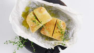 Sett ovnen på 175°. Skjær et dypt snitt i hvert rundstykke og pensle med smeltet smør blandet med hvitløk. Legg en tykk skive ost i hvert snitt og strø timianblader over. Gratiner rundstykkene i ovnen til osten smelter og brødene er gyllenbrune.