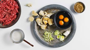 Bland egg og melk i en skål. Riv loffskiven i biter og legg dem i melken slik at de suger til seg væsken. Tilsett kjøttdeig, sennep, purreløk, salt og pepper og bland det sammen til en jevn farse. Fukt hendene og form farsen til kjøttboller.