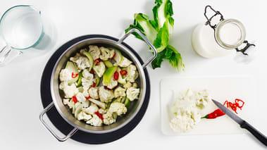 Del blomkålen i store biter og skrell og hakk hvitløk, løk og chili.
