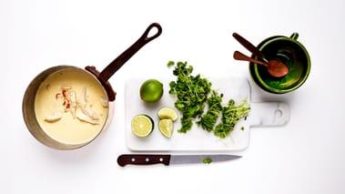 Tilsett kokosmelk, vann, limesaft og salt og kok opp. La det småkoke i 5 minutter. Legg i kyllingen. Kok opp suppen igjen, og la det småkoke i ca. 10 minutter.