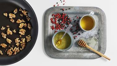 Grov hakk valnøttene og strø over sitrusskivene. Drypp over sirup og olivenolje og smak til med pepper. Server med en skål med yoghurt til å dyppe skivene i.