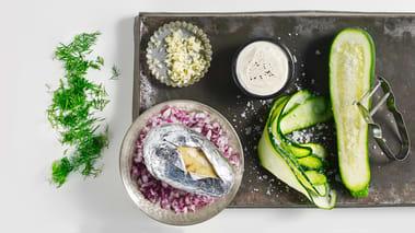 Skjær squashen i strimler og legg disse i et dørslag/sil. Strø på litt salt og rør rundt. La det stå i ca. 20 minutter. Finhakk rødløk og smak til yoghurten med dill, hvitløk, olje og eddik samt salt og pepper. Vend squashen i sausen og rør godt.