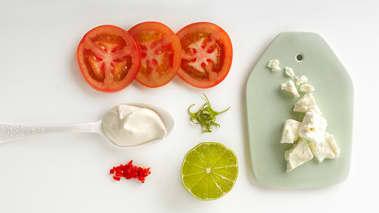 Skjær tomater i skiver og legg på et fat. Smuldre over fetaost i grove biter. Legg på klatter av lettrømme, og strø over finhakket chili og revet limeskall. Press over limesaft og hell på olivenolje, smak til med flaksalt.