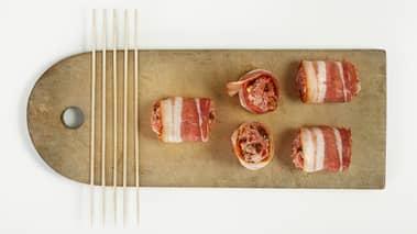 Form små, avlange kjøttboller og dekk de helt med bacon. Pass på at du former kjøttdeigen rundt spydet så de blir jevne og fine på oversiden.