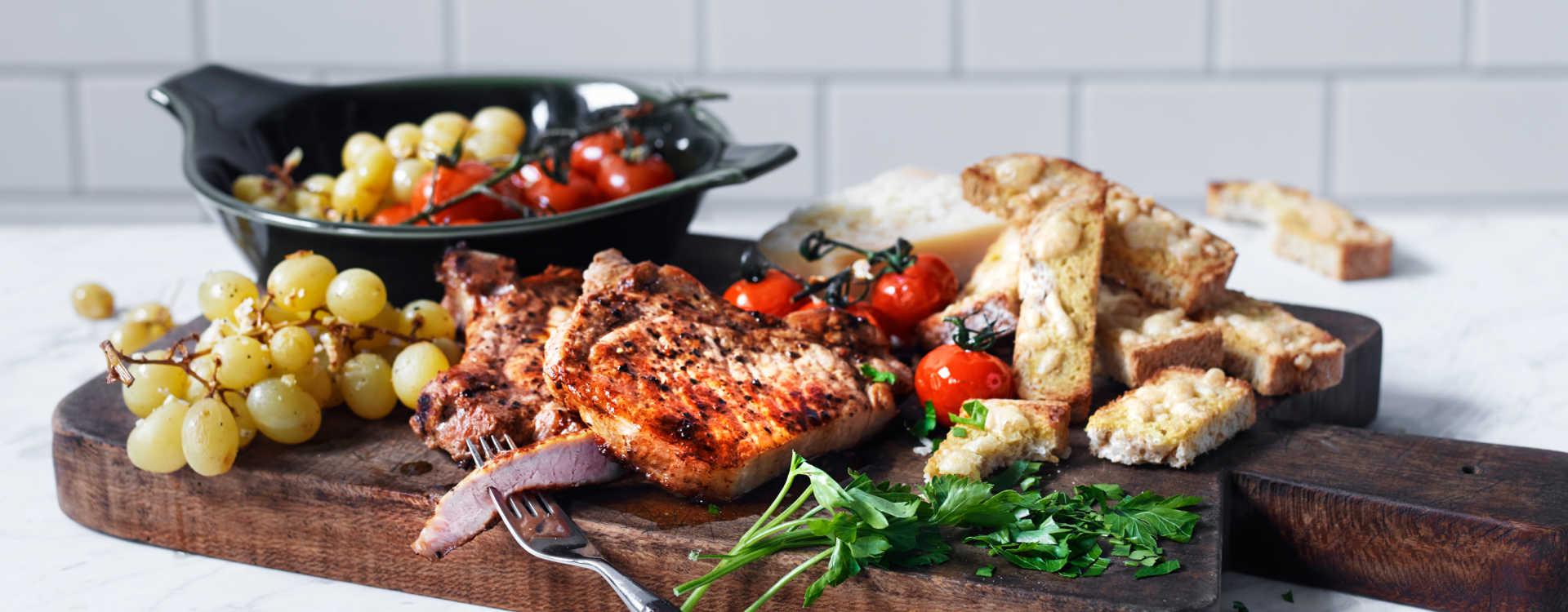 Grillet svinekotelett med varme tomater, druer og parmesanbrød
