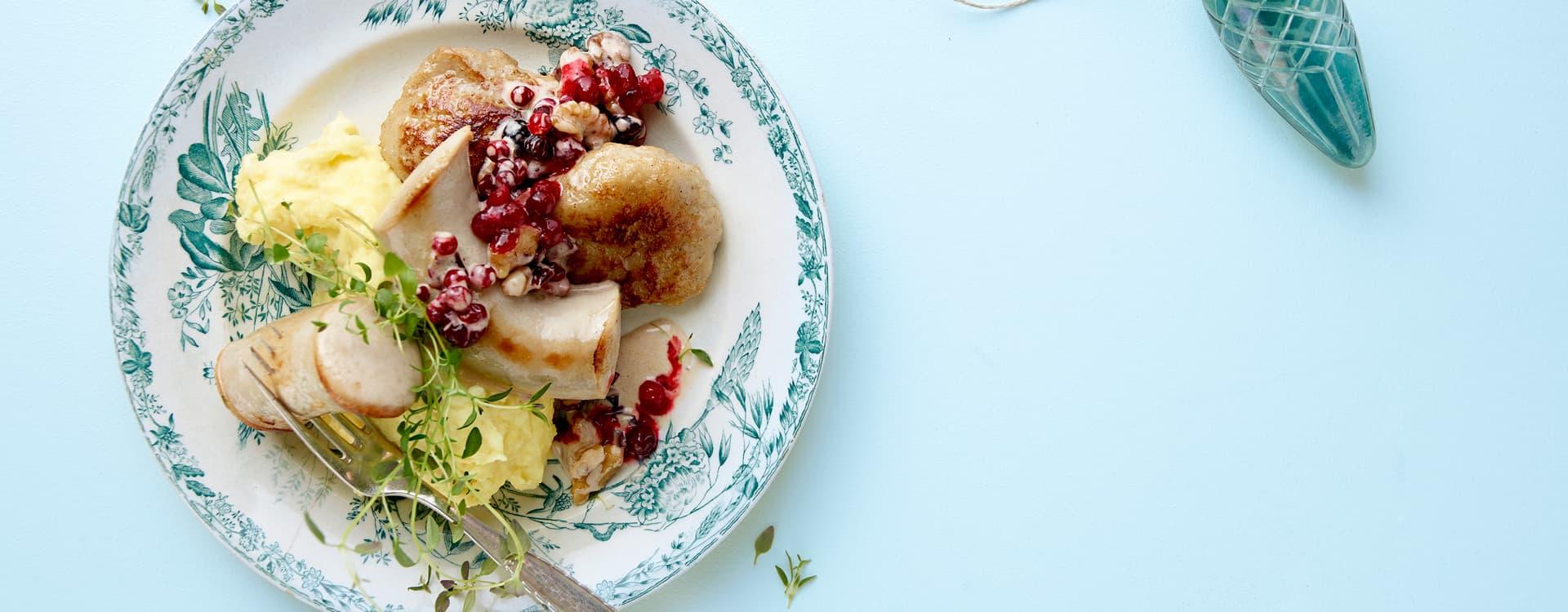 Medisterkake- og julepølsetallerken med mandelpotetpuré og tyttebærsaus