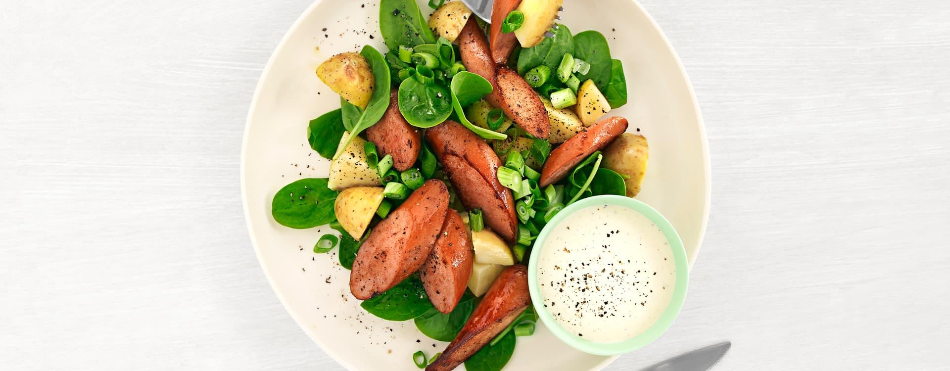 Spinatsalat med pølser, poteter og hvitløksrømme