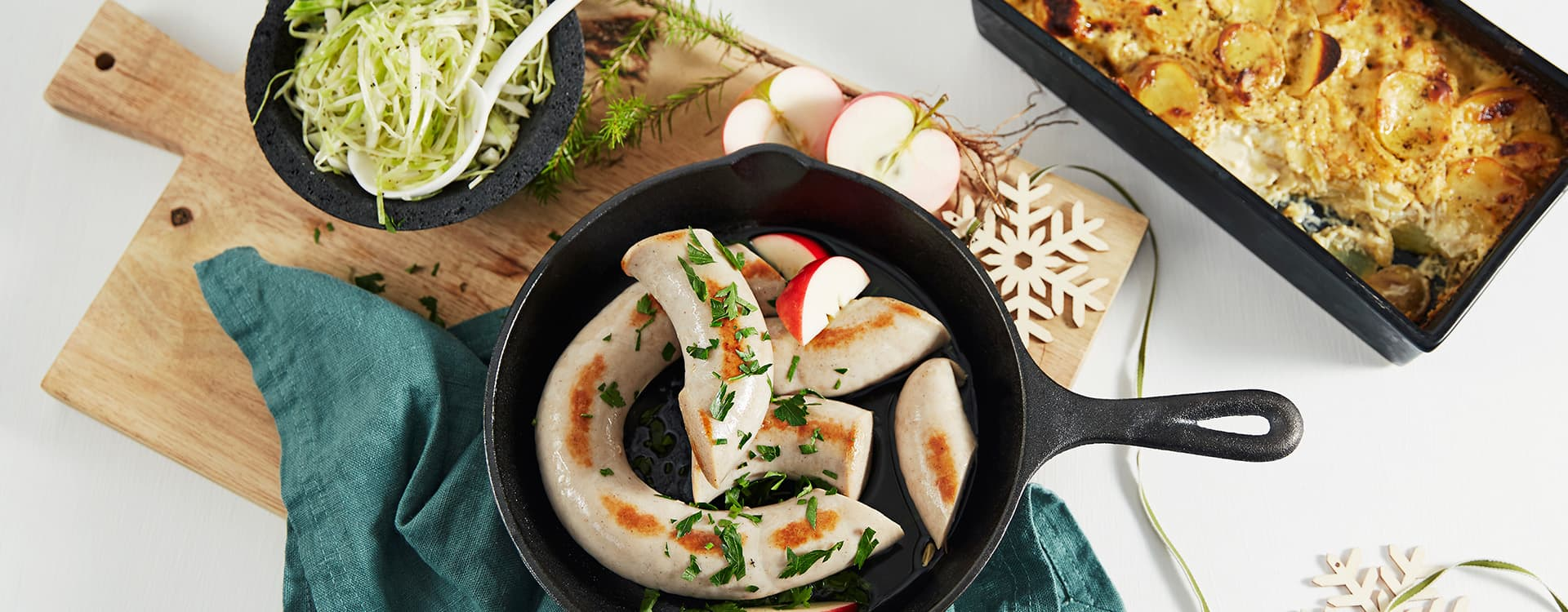 Grov julepølse med potetgrateng og syrlig kålsalat
