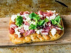 Pizza av focaccia med spekeskinke og mozzarella