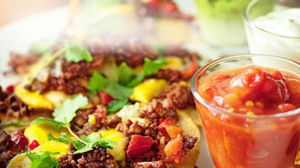 Nacho-tallerken med tacokrydret kjøttdeig, ost, jalapeños og guacamole