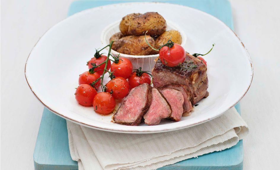 Baconsurret biff med ovnstekte poteter og grillede tomater
