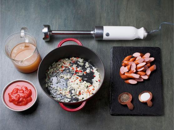 Fres løk, hvitløk og chili i olivenolje i en kjele. Tilsett tomater og kraft, kjør suppen jevn med en stavmikser, tilsett pølsebiter og kok opp. Smak til med salt og pepper og server med egg.