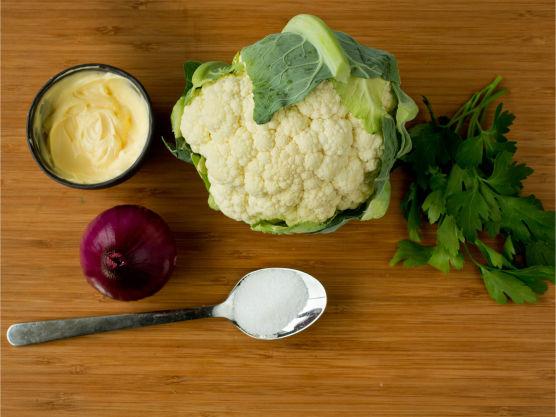 Del blomkålen i minibuketter og skjær rødløken i tynne strimler. Visp sammen majones, sukker og eddik.