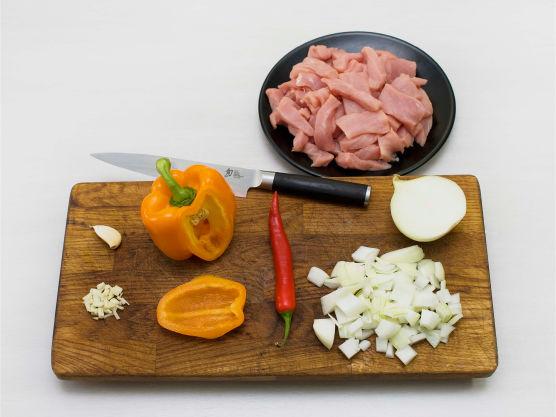 Skjær svinefileten i strimler og paprika i biter. Hakk løk, hvitløk og chili.