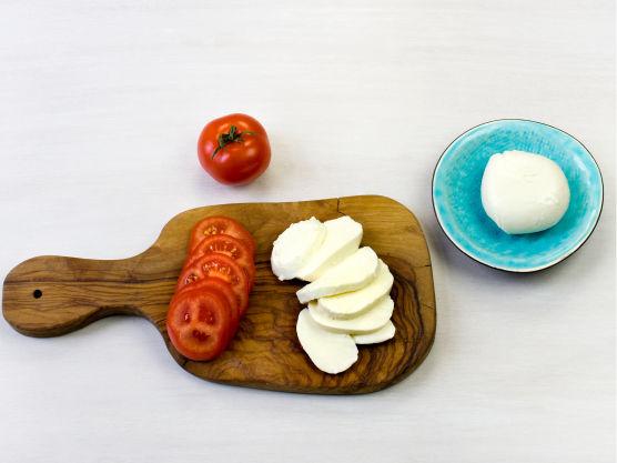 Skjær mozzarella og tomat i skiver.