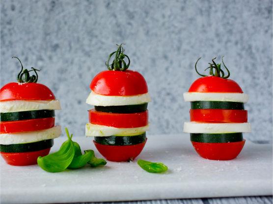 Skjær av en liten flik i bunnen av tomatene slik at de står stødig. Del hver tomat i tre skiver. Skjær squash og mozzarella i 8 skiver (ca. 1 cm tykke).