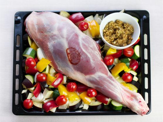 Ha 2 ss olivenolje i en langpanne. Stikk et steketermometer i den tykkeste delen av kjøttet og legg lammelåret i panne. Del aubergine, squash, paprika og løk i biter. Ha grønnsakene og hele cherrytomater i pannen, og stek lammelåret til det har kjernetemperatur på 70 °C, ca. 1 ½ time.