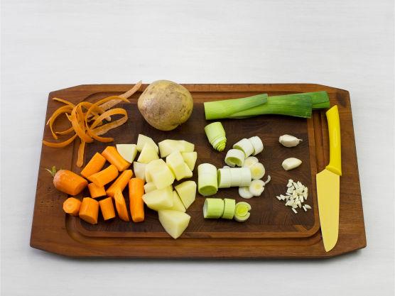 Grovhakk purre, gulrøtter, poteter og hvitløk, ha i en kjele og tilsett kraft.