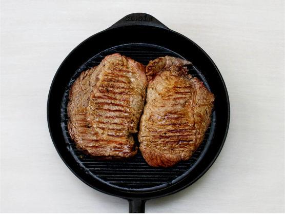 Ha olje i en stekepanne, og la denne bli skikkelig varm før du legger i biffene. Stek først så biffen får en brun og fin skorpe på den ene siden, snu den og skru ned varmen. Tilsett 2 ss smør, en kvast rosmarin og hvitløken i pannen. La smøret bli nøttebrunt. Bruk en skje og øs over biffene innimellom. Stek biffen til kjøttsaften pipler ut på oversiden, snu biffen og stek til det pipler på den andre siden.