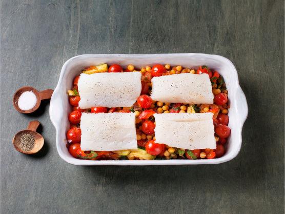 Ha grønnsaksblandingen i en ildfast form. Del fisken i porsjonsstykker, legg dem i formen og krydre med salt og pepper. Bak i ovnen på 180 °C i ca. 10 min.
