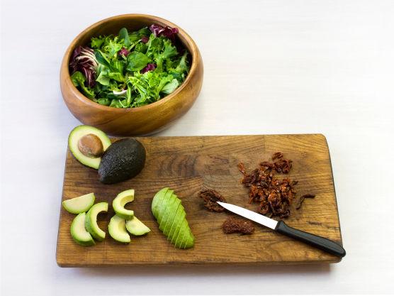 Vask salat, rens og del avokado, skjær tomat i skiver og del eggene. Knus valnøtter og bland i dressingen.