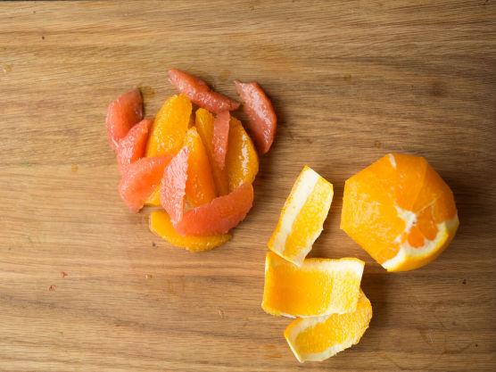 Skjær av topp og bunn på appelsinene og grapefrukten. Skjær av skallet, men pass på så du ikke skjærer vekk for mye. Bruk en skarp kniv og skjær ut «filetene» mellom de hvite hinnene. Press all saften fra appelsinrestene over i en bolle. Visp inn sitronsaft, honning og olivenolje. Smak dressingen til med salt og kvernet pepper.