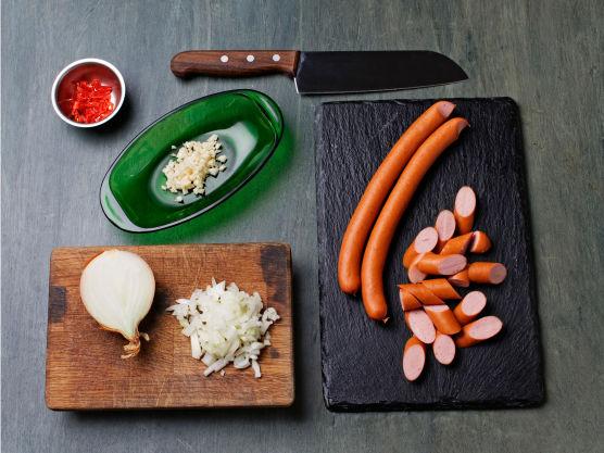 Hakk chili, løk og hvitløk og skjær pølser i biter.