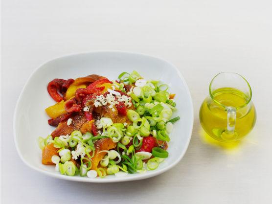 Skjær vårløk i skiver og hakk hvitløk. Rens og skjær paprika i strimler og bland med hvitløk, vårløk, olivenolje, salt og pepper, og server til kyllingen.