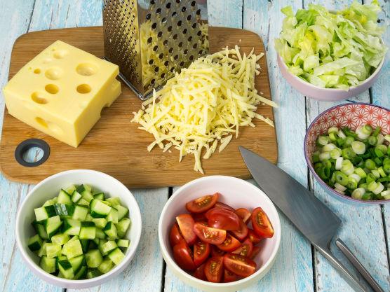 Skjær tomatene og agurken i terninger. Skjær salaten og vårløken i strimler. Riv osten på den grove siden på et rivjern.