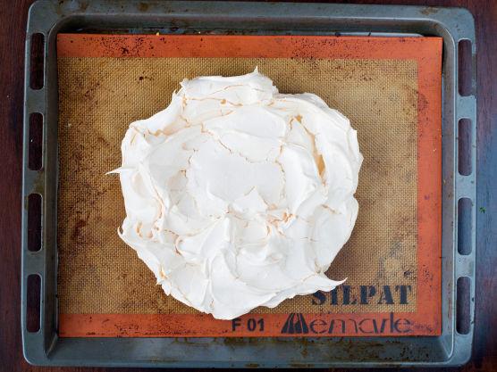 Form en stor rund marengskake (ca. 24 cm i diameter) på et stekebrett dekket med bakepapir eller bakeduk. Sett marengsen inn i ovnen og senk temperaturen til 140 grader. Stek marengsen i ca. 1 time. Den skal bli sprø på utsiden og være myk som krem i midten. Skru av ovnen, sett ovnsdøren på gløtt og avkjøl pavlovaen til romtemperatur inne i stekeovnen.