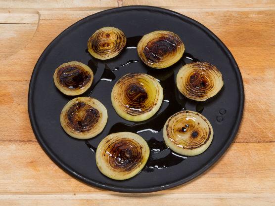 Brenn den ene siden på løkskivene i en tørr panne til den er mørk brun. Legg skivene i en langpanne og krydre med litt salt og pepper og dynk over halvparten av olivenoljen.