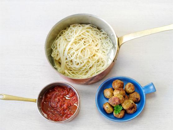 Kok spagetti etter anvisning på pakken, varm pastasausen i en kjele og anrett på tallerkener med noen kjøttboller på toppen.